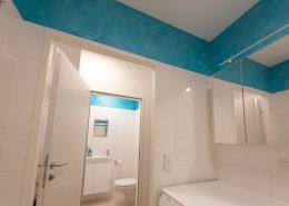 Belebung des Wandstreifens mittels türkiser Lasur, Blick von Badezimmer ins WC